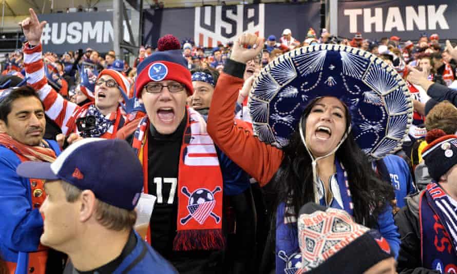 Hinchas de los dos lados de la porra cantando durante un partido de eliminatoria de Concacaf