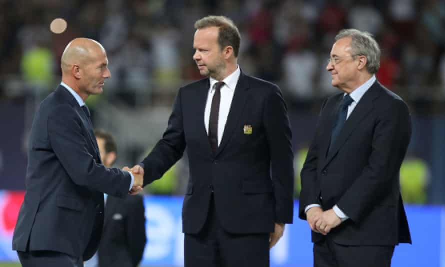 Manchester United's Ed Woodward pictured in 2017 shaking hands with the Real Madrid manager Zinedine Zidane while the Spanish club's president Florentino Pérez looks on.
