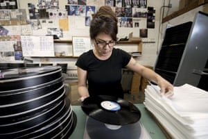 Maria Gamino quality checks an album before placing it in a sleeve