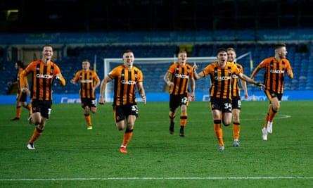 Hull players run towards the camera after Alfie Jones scored the winning penalty at Elland Road.