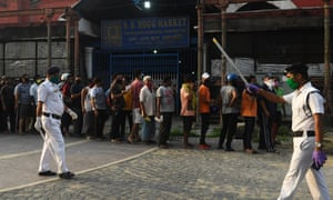 Police officials beside a queue outside a liquor shop in Kolkata to buy alcohol after the government eased a nationwide lockdown