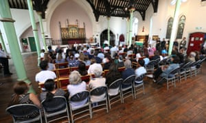 Members of the Grenfell Tower community attend a public meeting with representatives of the Gold Command structure at St Clement's church in west London, four weeks after the fire.