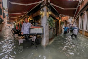 A restaurant owner looks at the flood waters in Venice, Italy