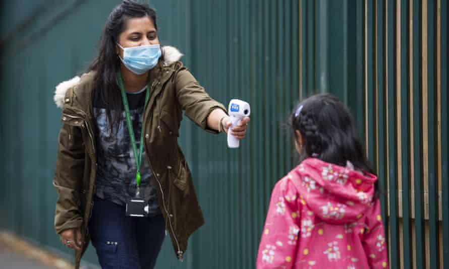 A London teacher checks a pupil's temperature before school.