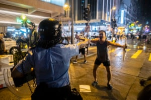 Protestor confronts an armed policeman in Hong King
