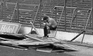 A Liverpool supporter sits in distress at Hillsborough following the carnage there on 15 April 1989