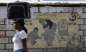 A woman walks carrying a suitcase on her head next to an Oxfam sign in Haiti