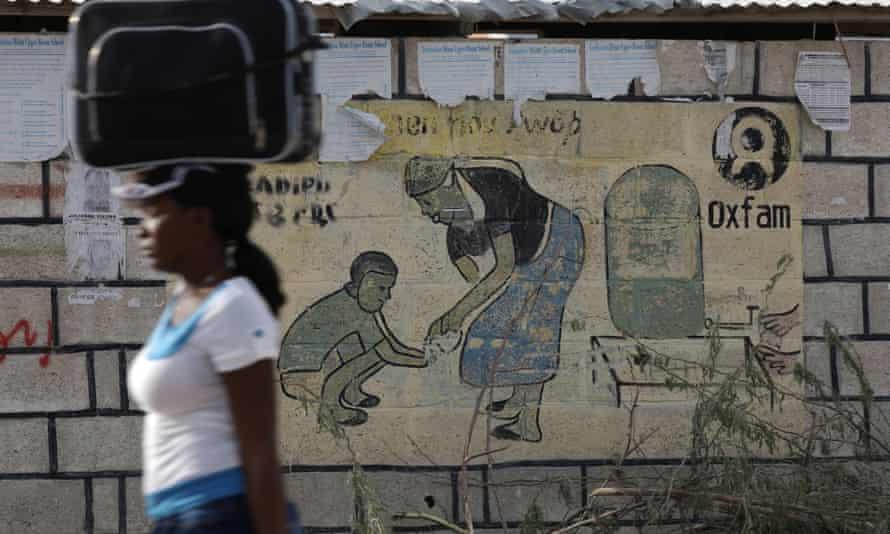 Woman walks past Oxfam sign near Port-au-Prince, Haiti