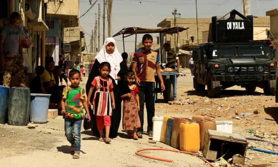A family walk along a street in west Mosul.