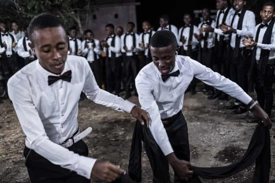 Bow-tied members of a dance troupe perform alongside wedding guests