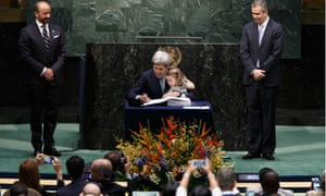 Kerry signs the Paris climate agreement with his granddaughter.