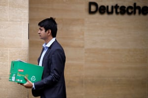 A man carries a box as leaves from the offices of German bank Deutsche Bank in central London on July 8, 2019
