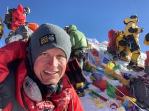 US guide Garrett Madison on Everest with flags and other climbers behind him