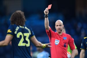 Referee Anthony Taylor shows red.