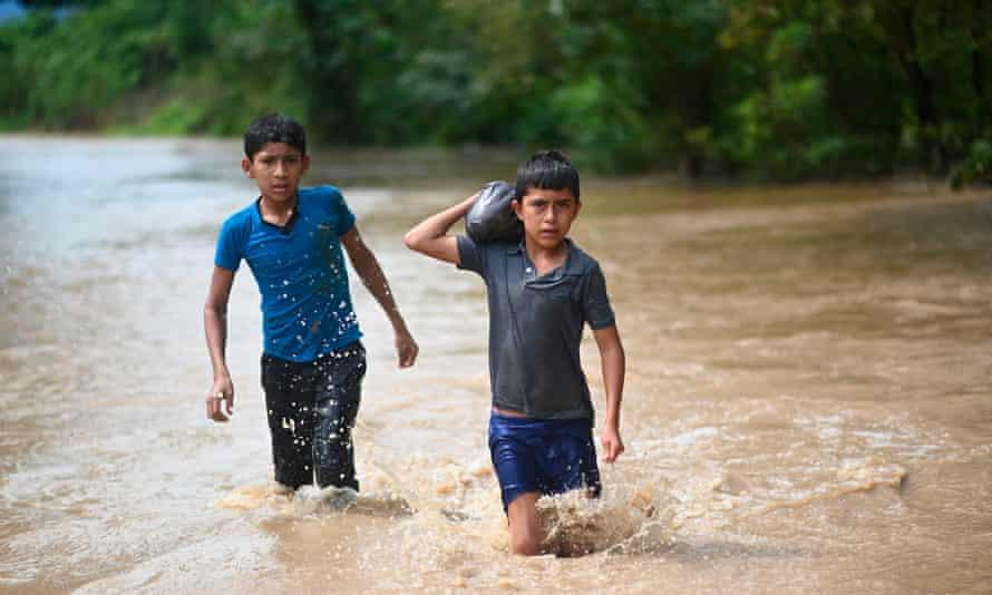 Children wade through flood water in Panzos, Alta Verapaz, 220 km north of Guatemala City