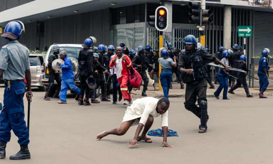 A riot policeman attacks a woman outside the Movement for Democratic Change headquarters in Harare