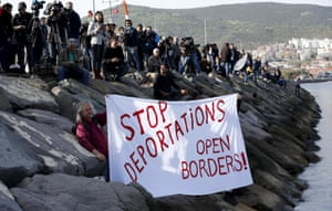 Activists hold a banner as a boat arrives in the Turkish coastal town of Dikili