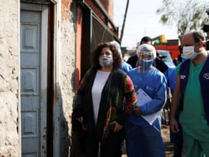 The Secretary of Health Access of the Argentinian Ministry of Health, Carla Vizzotti, stands outside a house with healthcare workers before asking residents if they are showing coronavirus symptoms, as part of the detectAR (detect) plan, in Villa Fiorito, on the outskirts of Buenos Aires, Argentina on 3 August, 2020.