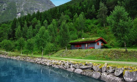 A Norwegian cabin by the water's edge; in the background is a heavily forested area of hills and mountains.