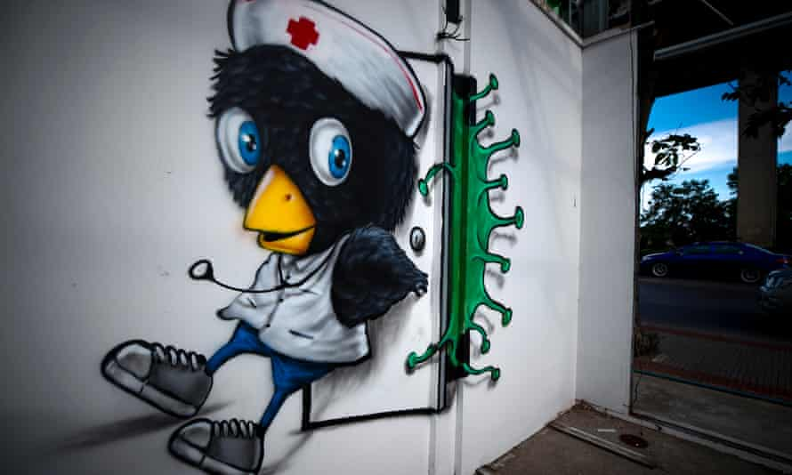 A view of a mural showing a bird nurse fighting to close the door on coronavirus by Thai street artist Muebon on a wall in Bangkok, Thailand