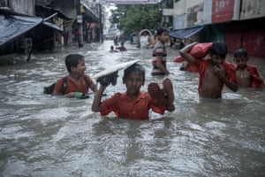 Schoolchildren wade through flood water on a street in Chaktai, Chittagong, Bangladesh