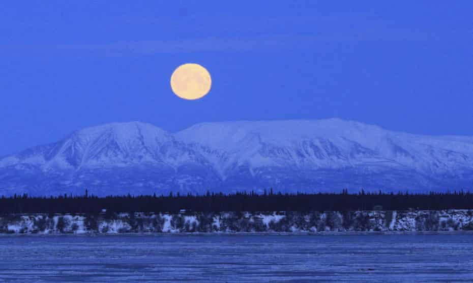 The moon sets over Mount Susitna, across Cook inlet, in Anchorage, Alaska.