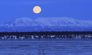 The moon sets over Mount Susitna, known locally as Sleeping Lady, across Cook Inlet in Anchorage, Alaska