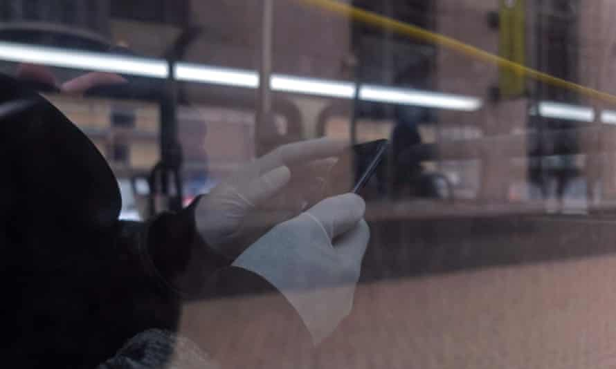 A passenger wears gloves for protection on a bus in Detroit, Michigan on 24 March 2020.