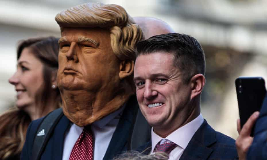 Stephen Yaxley-Lennon stands beside a man in a Donald Trump mask as he addresses supporters outside the Old Bailey in London, England.