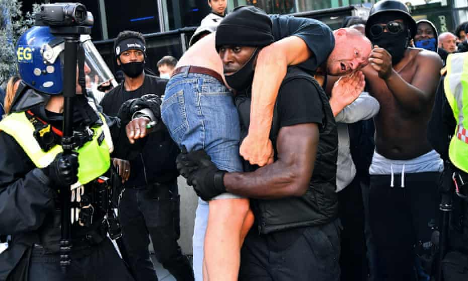 Patrick Hutchinson carries far-right counter-protester Bryn Male to safety