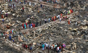 People survey the wreckage after a shanty town fire in Dhaka.
