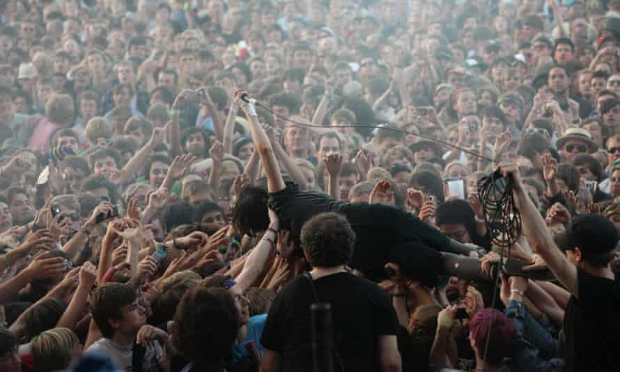 Alice Glass of Crystal Castles stagedives into a moshpit.