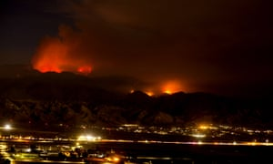 The Apple fire burns behind mountains near Beaumont, California Sunday.