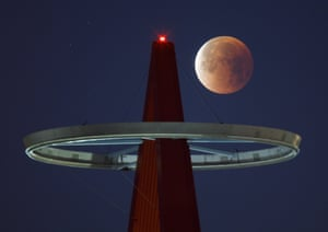 The moon appears to orbit the sign of the Angel stadium in Anaheim, California