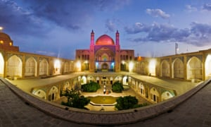 Dusk delight … the Agha Bozorg mosque in Kashan, Iran. Panorama of Agha Bozorg school and mosque in Kashan in evening with purple lights on, Iran, with small garden inside