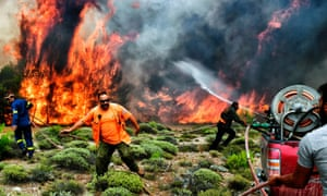 Firefighters and volunteers tackle the wildfire at the village of Kineta, near Athens.