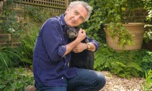 Writer Simon Garfield kneeling down in his garden to embrace his dog Ludo.
