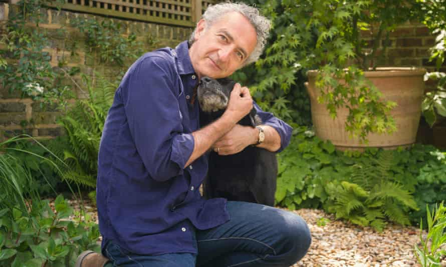 Writer Simon Garfield kneeling down in his garden to embrace his dog Ludo.
