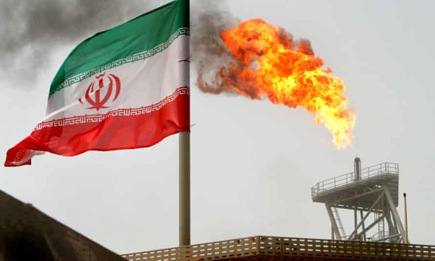 A gas flare on an oil production platform on Kharg Island, alongside an Iranian flag.