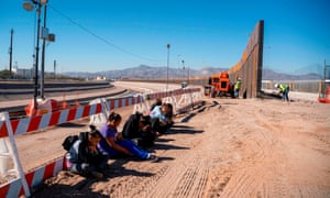 Salvadoran migrants wait for a transport to arrive after turning themselves in to US border patrol by the border fence under construction in El Paso, Texas, last week.