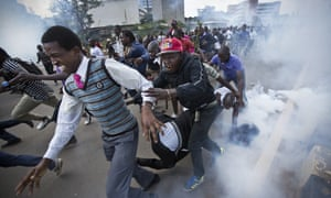 Crowds flee from teargas grenades fired by riot police during the protest in Nairobi.