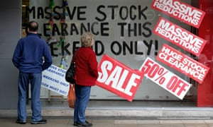Shoppers walk past a shop window advertising a closing down sale.