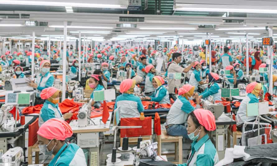 Hundreds of workers, identically clad, operate sewing machines at a garment factory