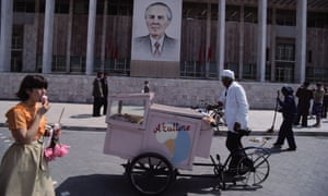An ice-cream vendor and pedestrians pass a building with a portrait of Enver Hoxha c. 1980