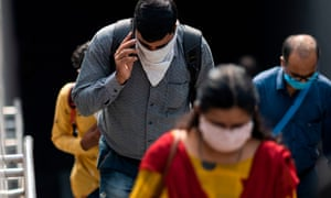Commuters wearing face masks as a preventive measure against coronavirus walk out of a metro station in New Delhi on 16 September 2020.