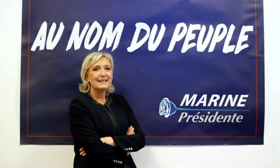 Marine Le Pen poses in front of a poster for her 2017 French presidential election campaign.