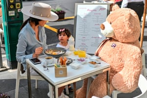 Customers sit with a teddy bear used for social distancing at a restaurant in the Polanco neighbourhood of Mexico City.