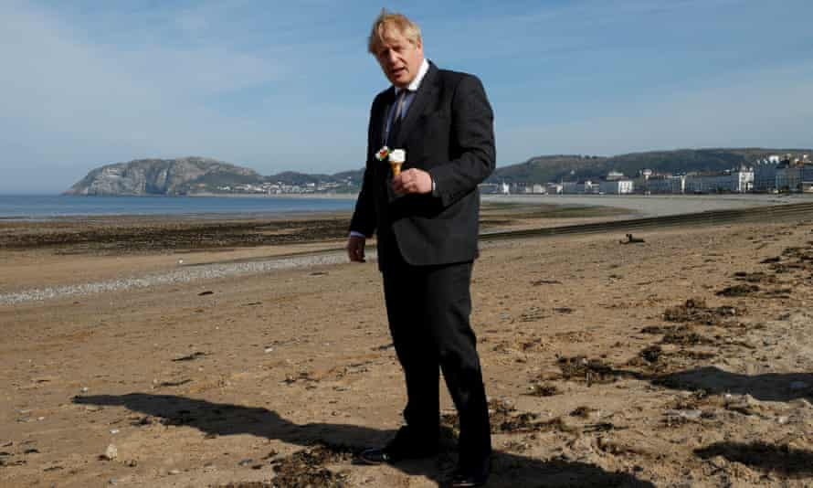 Boris Johnson holds an ice-cream on the beach as he campaigns in Llandudno, Wales ahead of elections on April 26