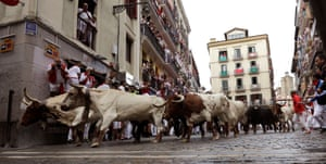 Runners stay wide as the herd from the Puerto de San Lorenzo ranch come into a sharp corner in the third running with the bulls