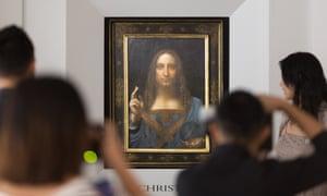 People take photos of Leonardo da Vinci's Salvator Mundi painting.